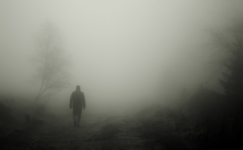 Person walking away in the fog, representing faking their death to escape