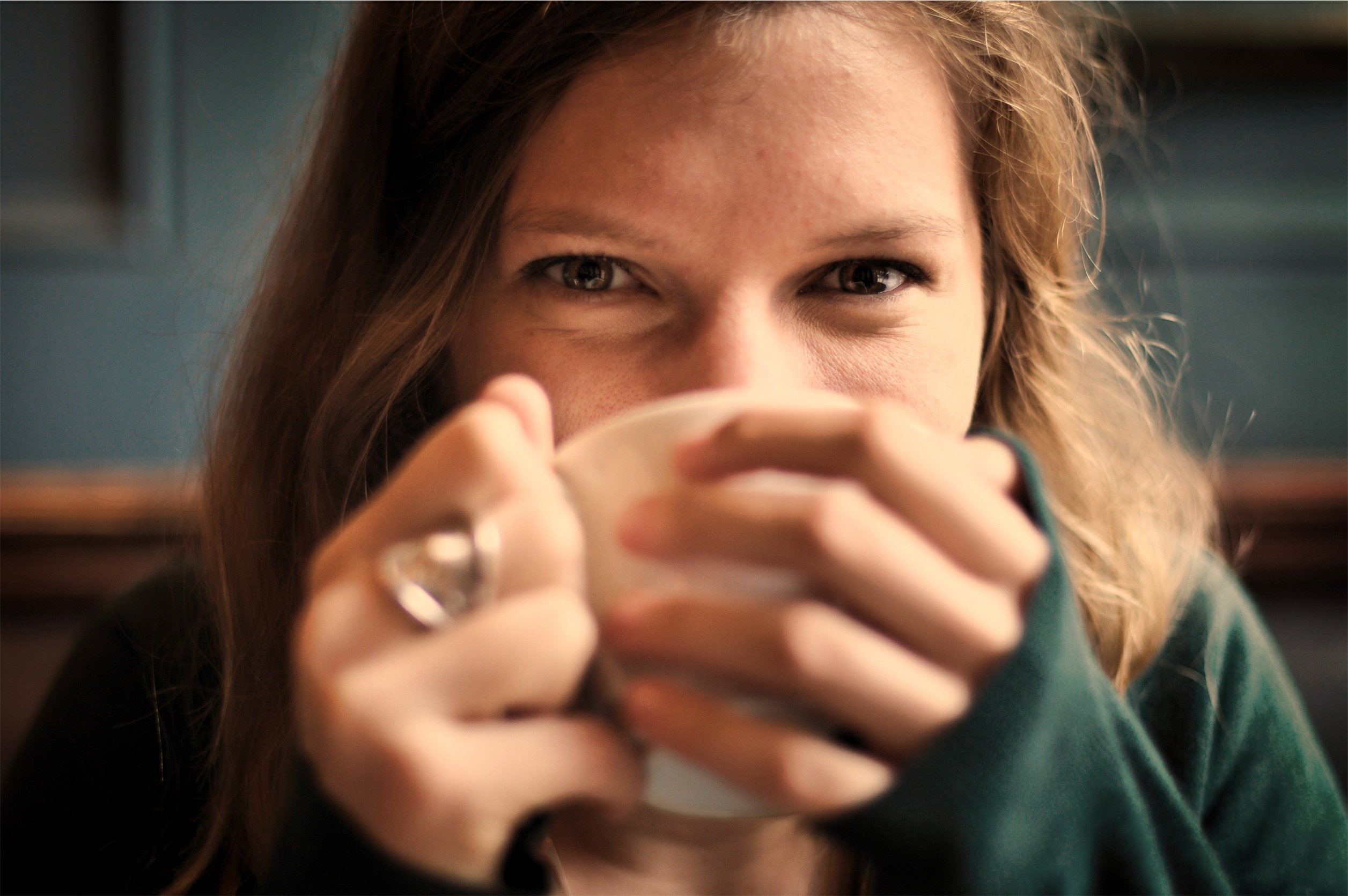 Smiling woman drinking coffee, feeling happy about the cost of hiring Melbourne Investigations
