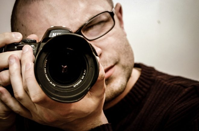 Man taking a photograph while conducting a private investigation