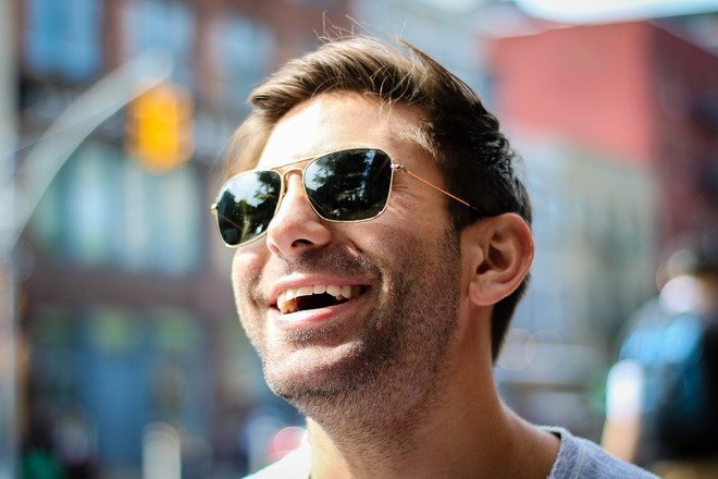 Smiling man wearing sunglasses showing he is reassured by an approachable female investigator